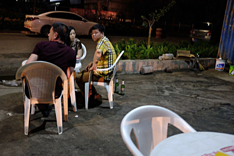 People sitting on chairs at night