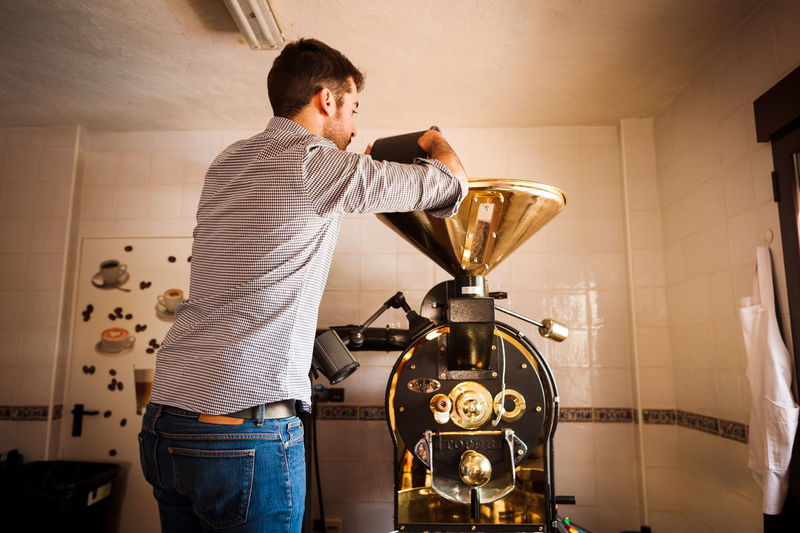 Barista preparing coffee in machinery at cafe