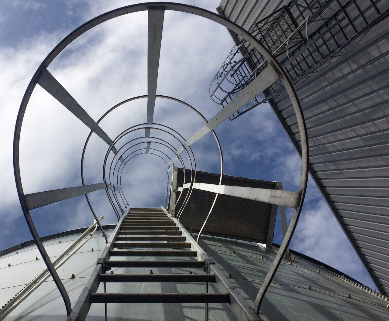 architecture, built structure, staircase, railing, sky, steps and staircases, low angle view, cloud - sky, metal, day, no people, building exterior, nature, spiral, arch, outdoors, building, directly below, ladder, steel