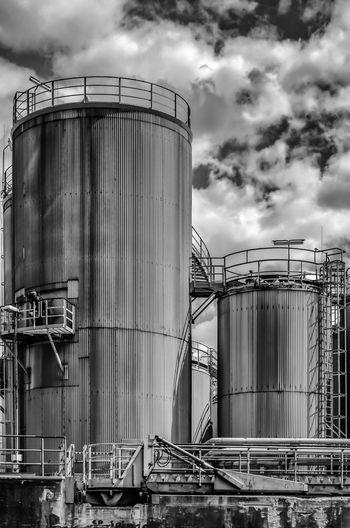 Storage tanks at industry against sky