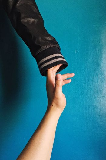 Cropped hand of person touching jacket sleeve against blue wall