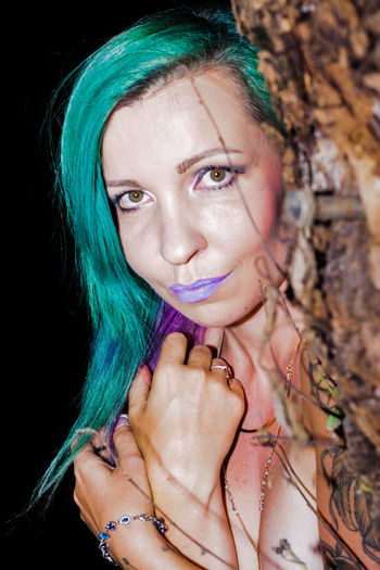 Portrait of naked woman with green dyed hair standing by tree at night
