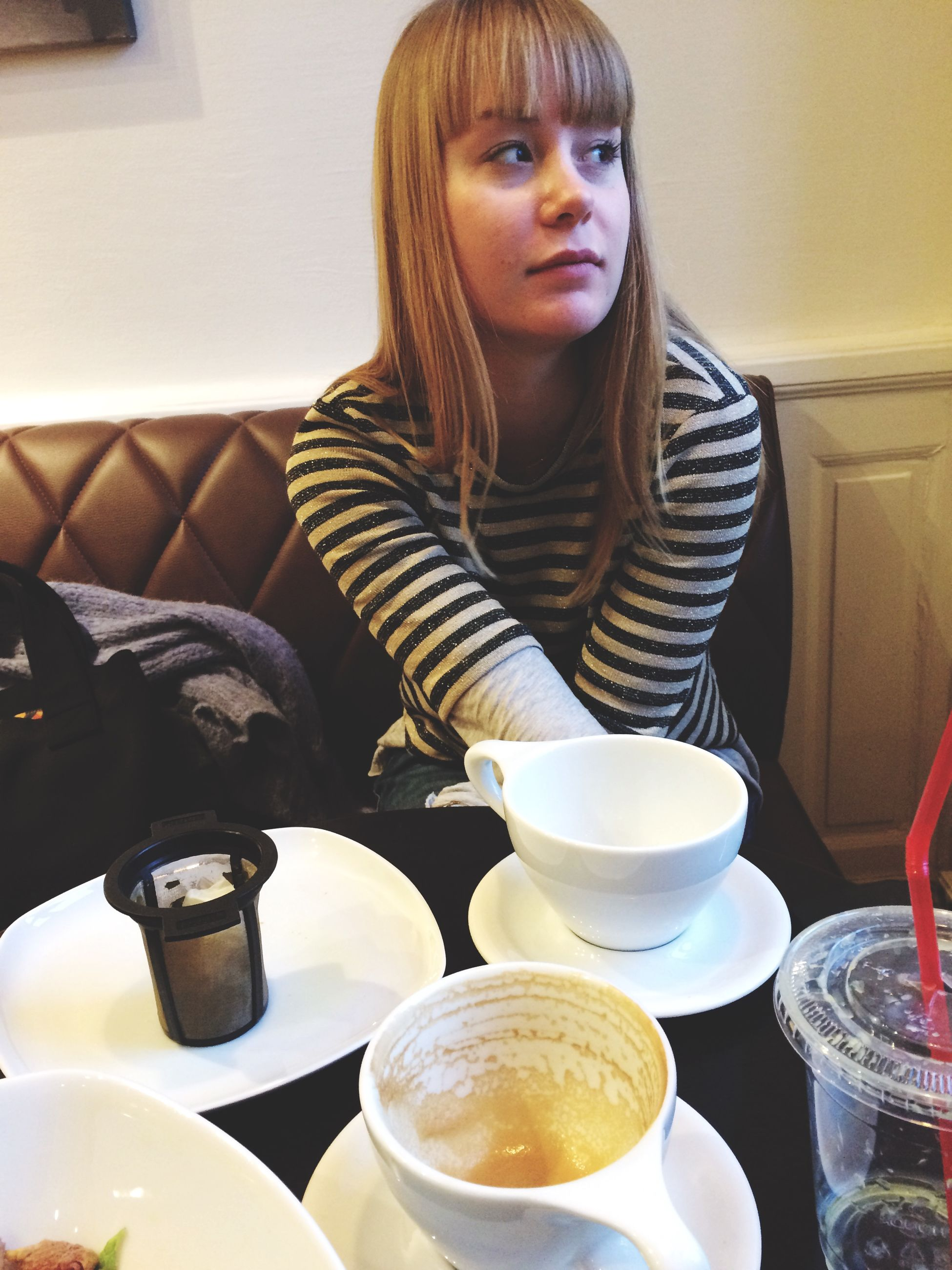 indoors, food and drink, lifestyles, young adult, drink, leisure activity, young women, refreshment, casual clothing, front view, coffee cup, table, sitting, portrait, looking at camera, person, standing, food