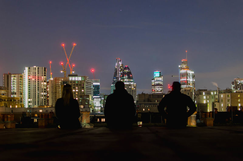 Rear view of friends sitting against 30 st mary axe in city at night