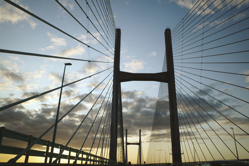 Low angle view of suspension bridge against cloudy sky