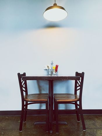 Table Indoors  Chair No People Home Interior Low Angle View Chairs Restaurant Dinner Dinner For Two Ketchup Mustard Forks Knives Wood Light Wall White Black Brown Day