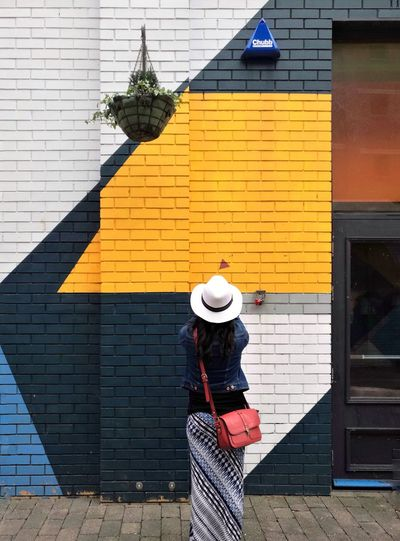 Rear view of woman standing against building