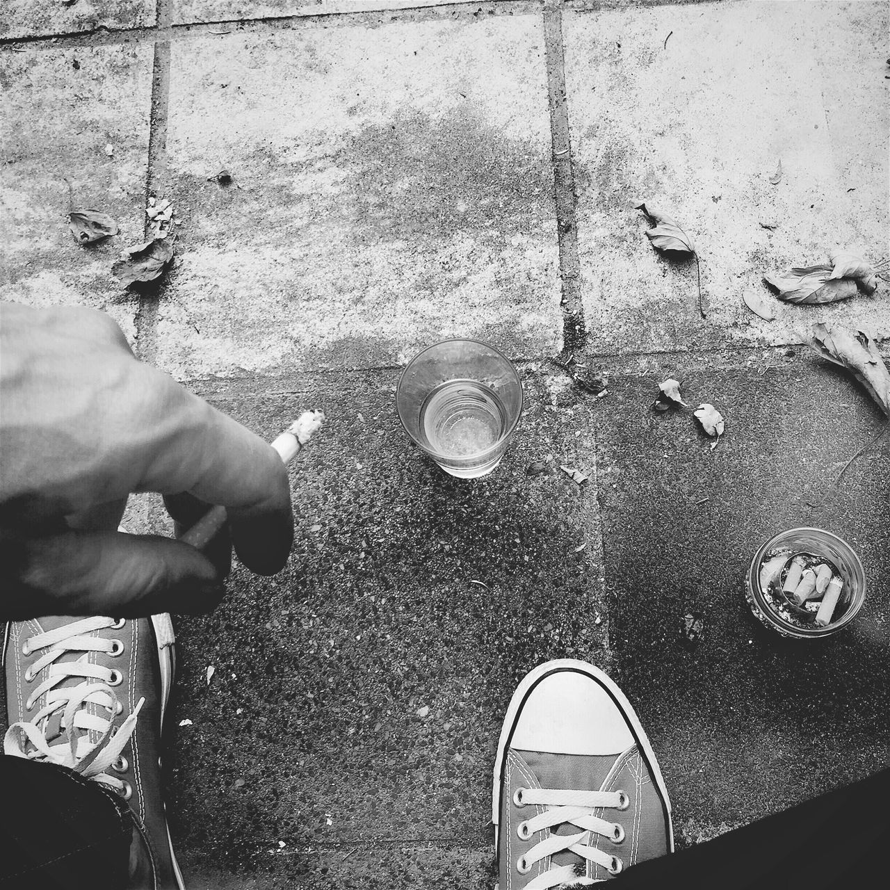 Low Section Of Man Holding Cigarette By Drink On Sidewalk