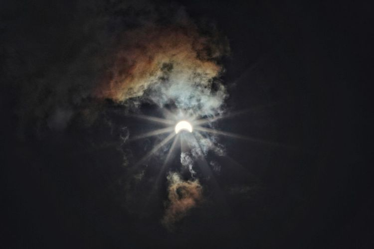 Low angle view of illuminated light against sky at night