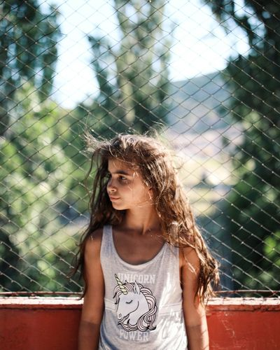 Close-up of girl looking away while standing against chainlink fence