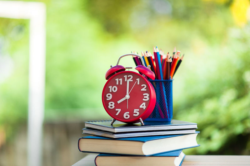Close-up of colored pencils in desk organizer with books and alarm clock at home
