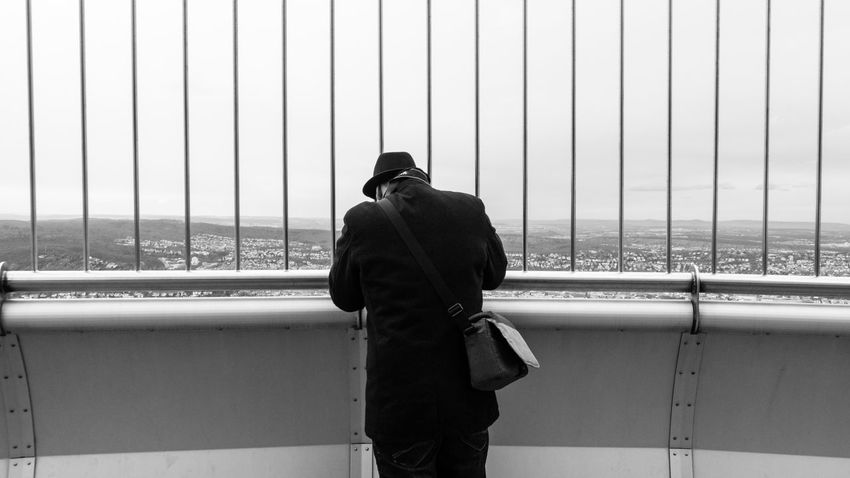 The detective Adult Adults Only Black & White Black And White Blackandwhite Day Detective EyeEm Best Shots Germany Instagram Leisure Activity Men One Man Only One Person Only Men Outdoors People Photography Railing Real People Rear View Sky Standing Three Quarter Length Warm Clothing EyeEmNewHere This Is Masculinity