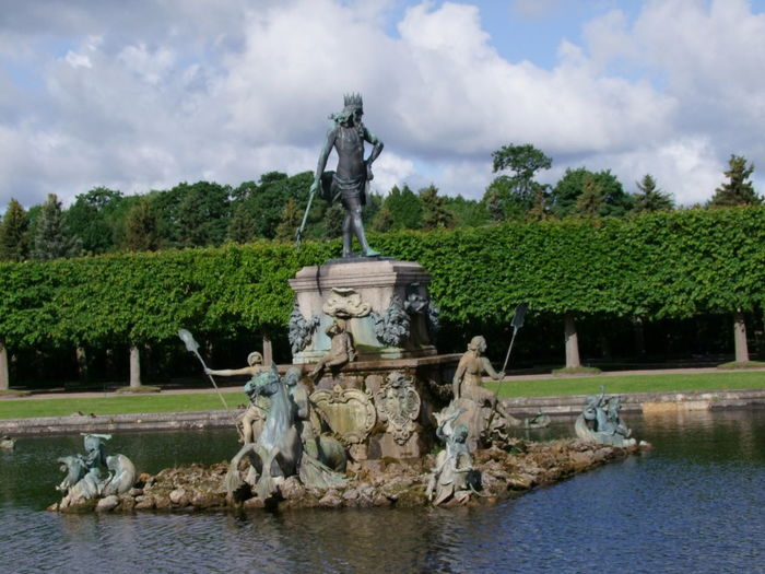 Neptune Fountain, Peterhof Beauty In Nature Blue Sky White Clouds Composition Fountain Grass Hedge Idyllic Mythology Neptune Fountain No People Outdoor Photography Palace Paris Peterhof Palace Reflection Ripples In The Water Russia Saint Petersburg Sunlight Tourist Attraction  Tourist Destination Tranquil Scene Tranquility Trees Water