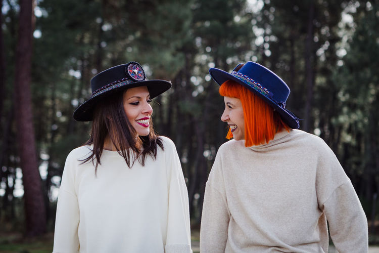 Smiling women wearing hat standing in forest