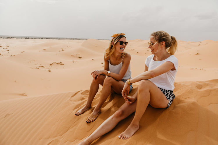 Cheerful Friends Sitting On Sand At Desert Against Sky