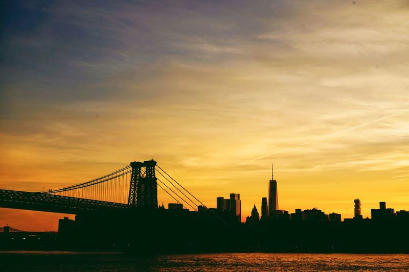 View of bridge over city at sunset