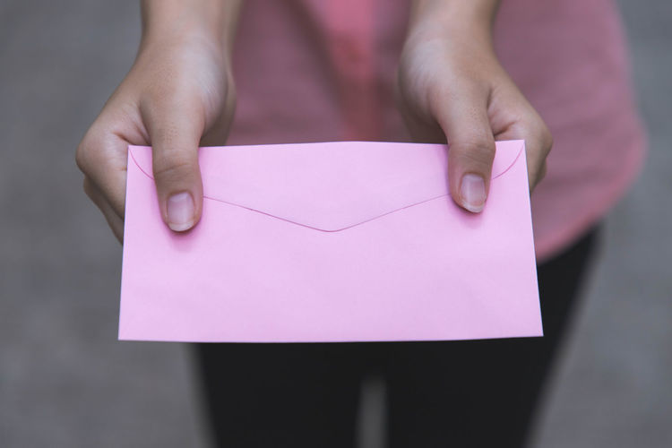 Midsection of woman giving pink envelope