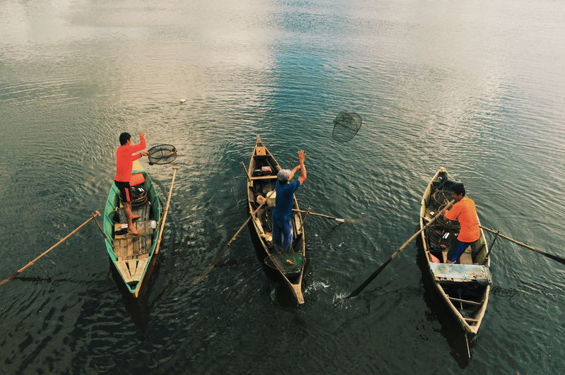 High angle view of men boating on lake
