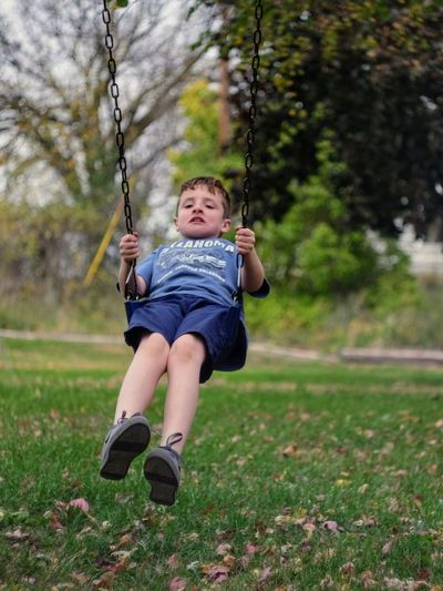 Full length of boy enjoying on swing at park