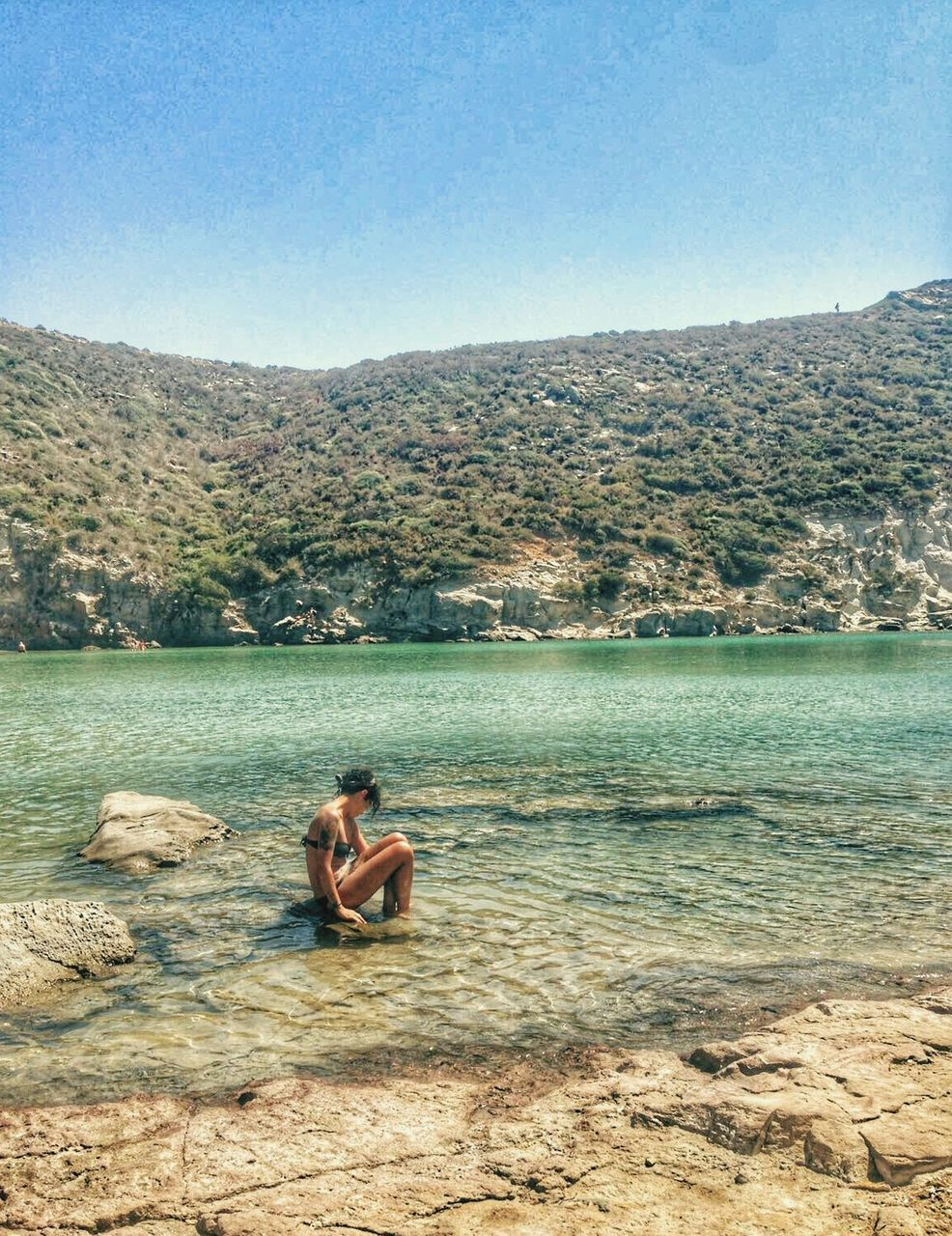 MAN SITTING ON SHORE AGAINST MOUNTAINS