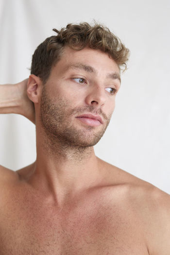 Portrait of young man looking away against white background