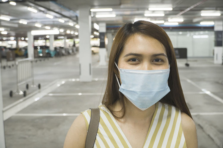 Portrait of woman wearing mask standing in parking lot