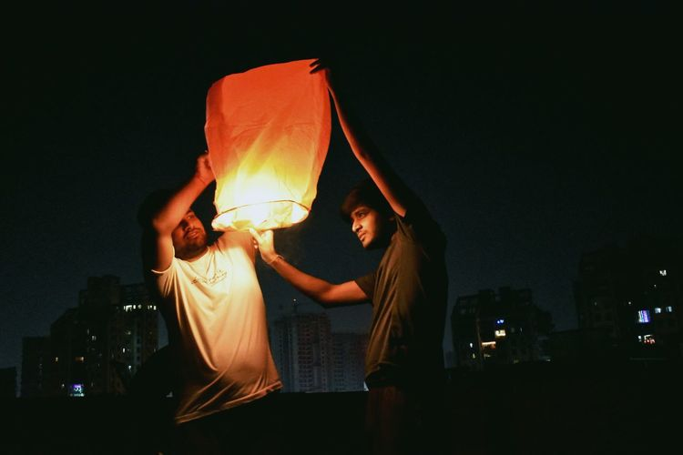 Friends holding illuminated paper lantern at night