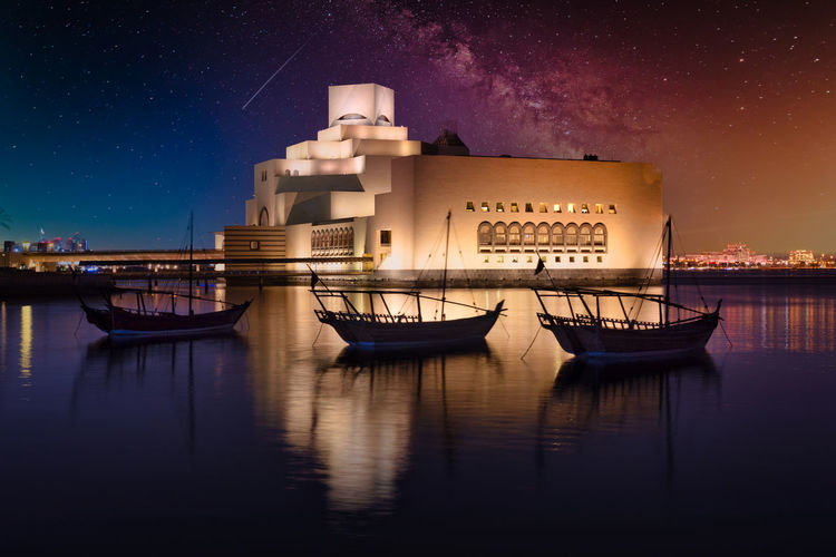 Boats moored in illuminated building against sky at night