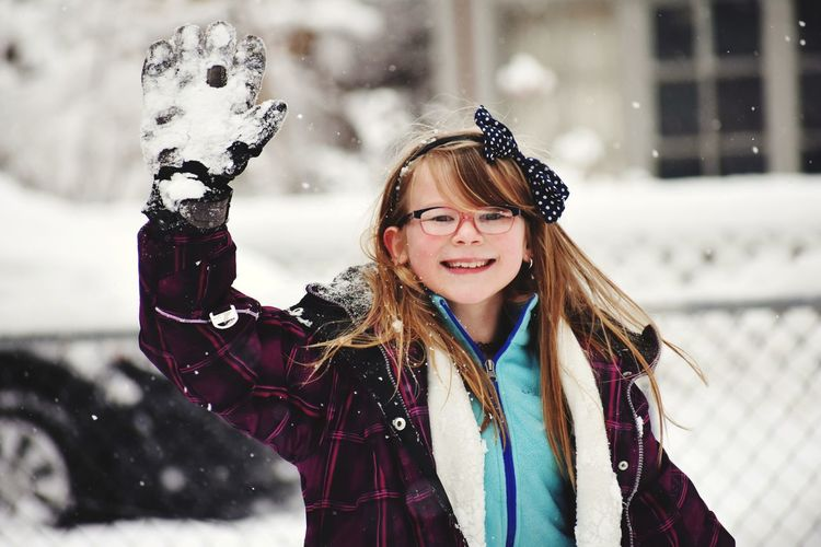Portrait of smiling girl waving hand during snowfall