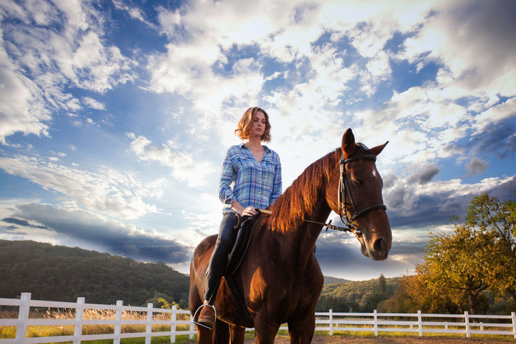 Woman riding horse in ranch against sky