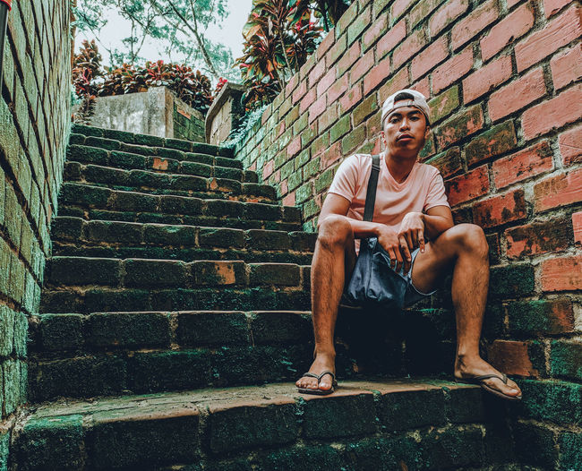 Man sitting on staircase against wall