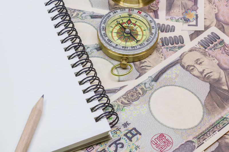 pencil on note book, compass with banknotes ten thousand yen for business and financial concept. Clock Close-up Compass Day Finance Indoors  Japan Money Navigational Compass Still Life Table Time White Background