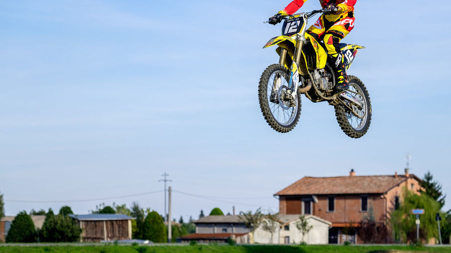 Low section of man performing motorcycle stunt in mid-air