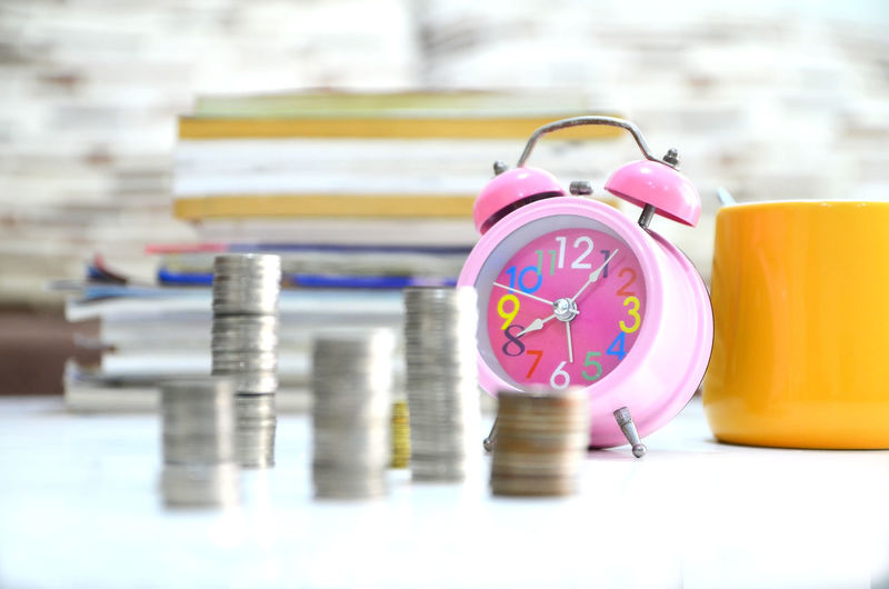 Stacked coins and alarm clock on desk