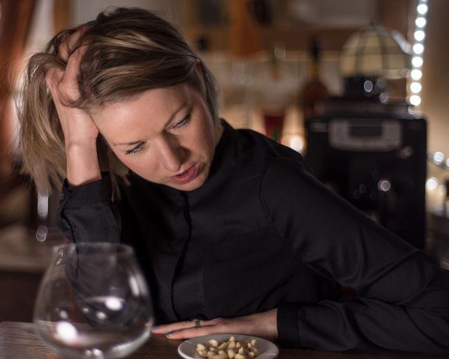 Close-Up Of Tensed Woman Having Nuts At Bar