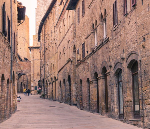 San Gimignano, Tuscany, Italy Golden Italia Travel Tuscany Alley Arch Architecture Building Building Exterior Built Structure City Direction Footpath History Incidental People Italy Old Outdoors San Gimignano, Street The Past The Way Forward Town Travel Travel Destinations