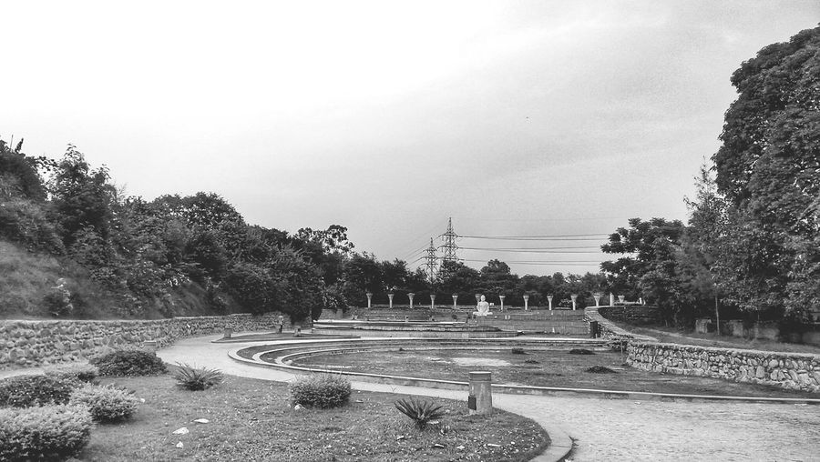 The garden of silence Beauty In Nature No People Field Nature Beauty In Nature City Nature Travelphotography Black And White Collection  Black&white Explorer The Way Forward Freshness Travelgram Hardwork Built Structure Grass Road Sign