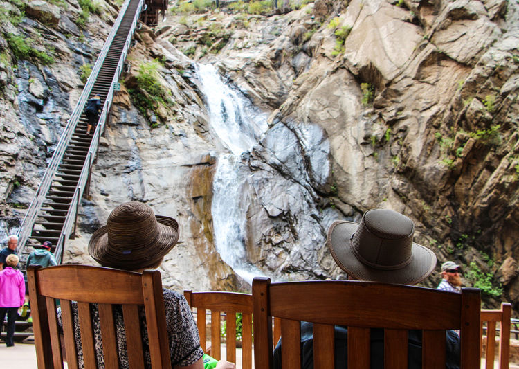 Tourists Sitting On Chair At Seven Falls In Colorado Springs