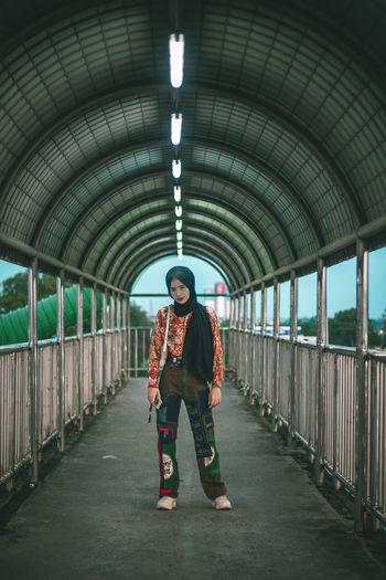 Full length portrait of girl standing on footbridge