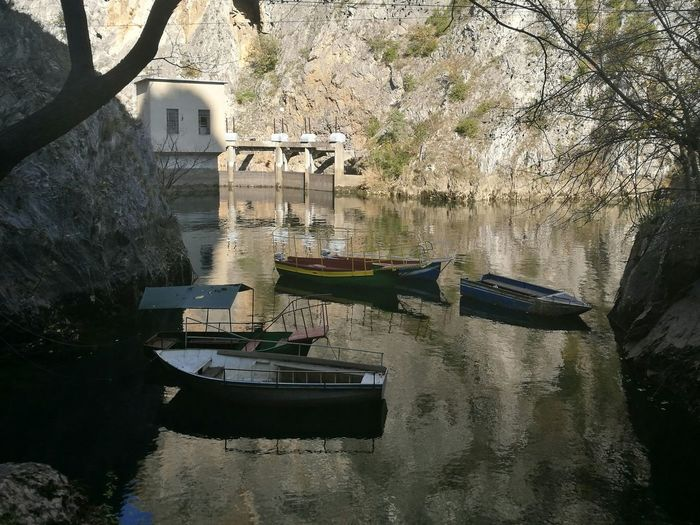 Boats in water against trees