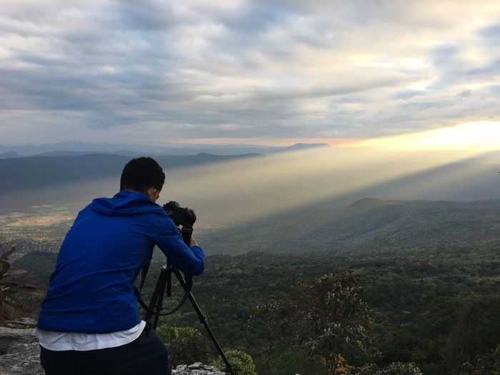 Rear View Of Man Photographing While Standing On Cliff Against Mountains
