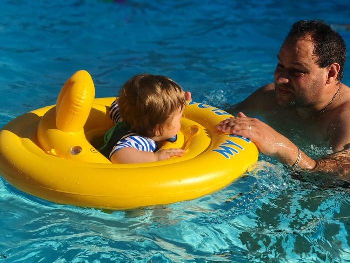 Father with son in swimming pool