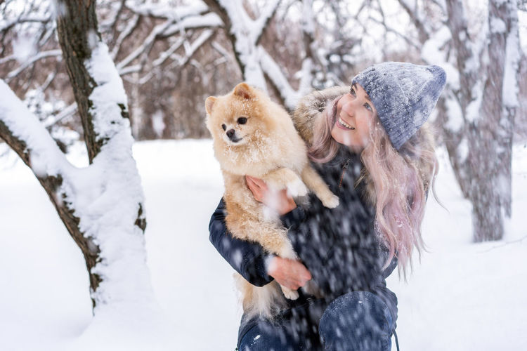 Young Woman Carrying Dog While Crouching In Snow During Winter