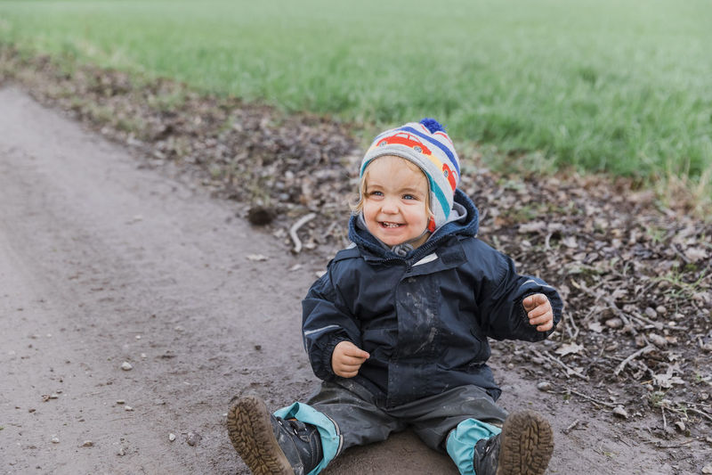 Happy toddler girl sitting with muddy pants on dirt road – Kempen, Germany Adventure Baby Boot Carefree Casual Caucasian Cheerful Child Childhood Close-up Coat Curiosity Cute Dirt Dirty Excitement Exploring Field Finger Footpath Front View Full Length Fun Germany Girl Hand Happy Jacket Joy Land Looking At Camera Messy Mud Nature One Outdoors Pants People Playing Pointing Portrait Raincoat Road Sitting Smiling Toddler  Unhygienic Weather Wet Winter One Person Innocence Males  Boys Real People Day Happiness Clothing Warm Clothing The Portraitist - 2019 EyeEm Awards