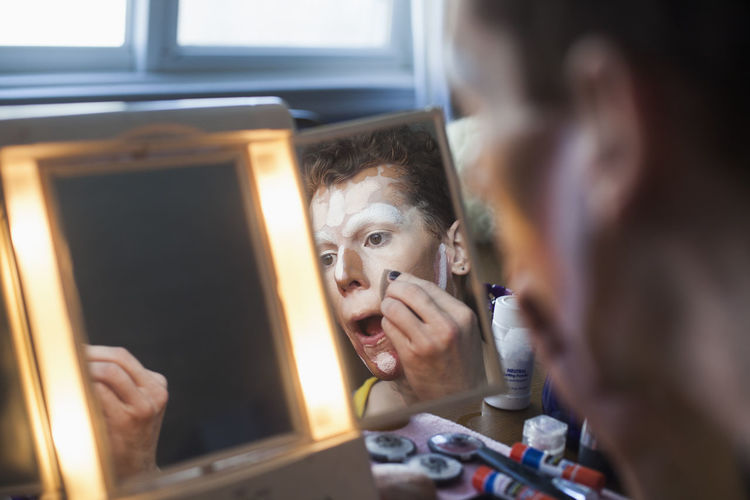Man applying drag makeup in mirror