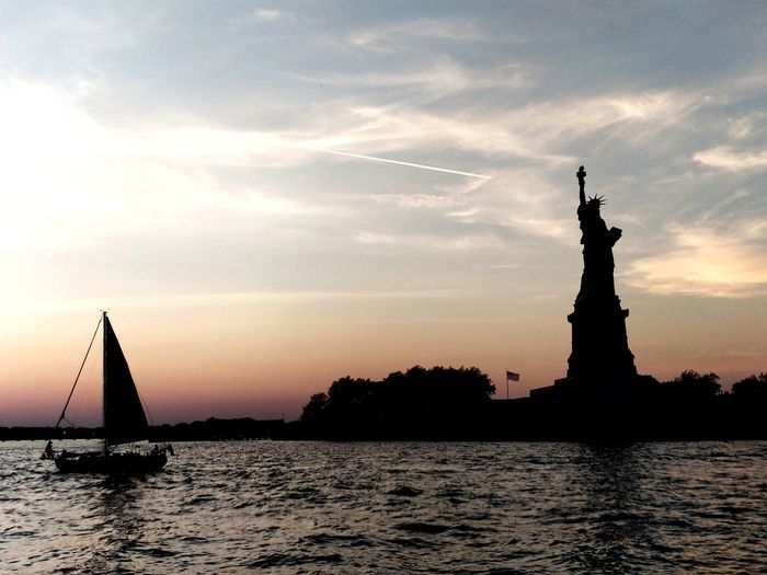 she stands up tall to show the rest of the world they don't stand a chance ... Statue Of Liberty New York City EyeEm Selects Nautical Vessel Politics And Government Water Sunset Statue City Cityscape Sculpture Silhouette Politics