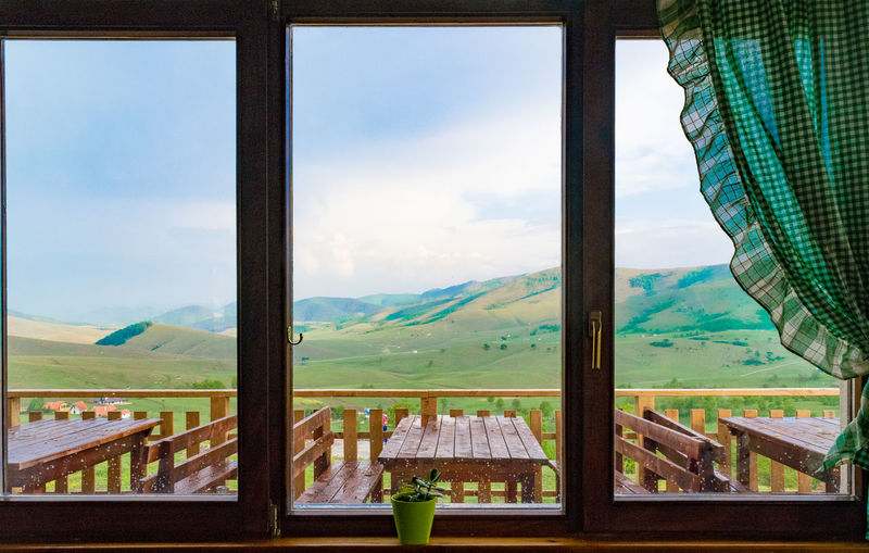 Scenic View Of Mountains Against Sky Seen Through Window