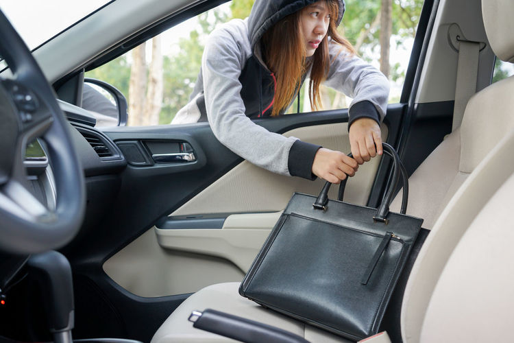 Female mugger stealing purse from car