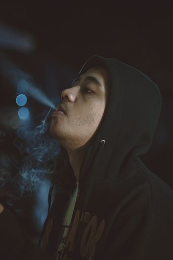 Close-up of man exhaling smoke at night