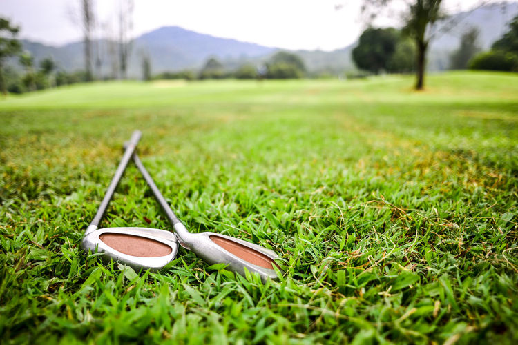 Surface level view of golf clubs on grass